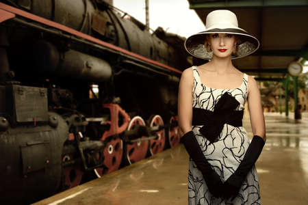 railway history: Woman in hat on a train station Stock Photo