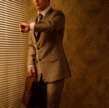 cronógrafo: Retro hombre de negocios mirando su reloj Foto de archivo