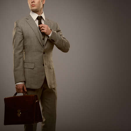 Businessman with a briefcase isolated on grey Stock Photo - 15473175