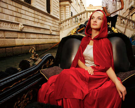 Beautiful woman in red cloak riding on gondola Stock Photo - 15473265