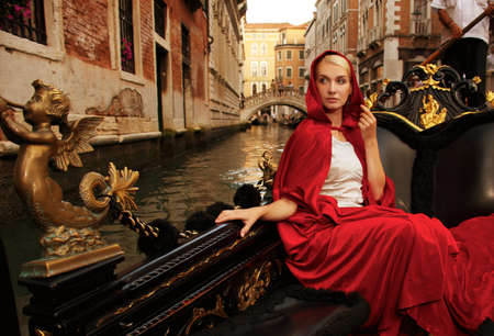 Beautiful woman in red cloak riding on gandola photo