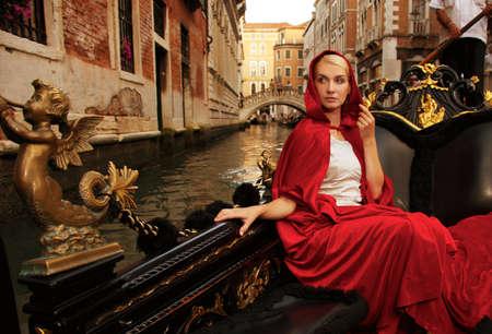 gondolas: Beautiful woman in red cloak riding on gandola
