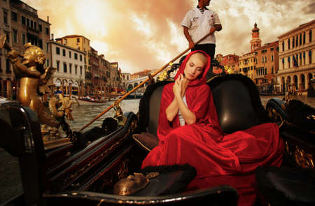 Beautiful woman in red cloak riding on gondola Stock Photo - 15473306
