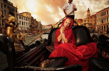 venice bridge: Beautiful woman in red cloak riding on gondola
