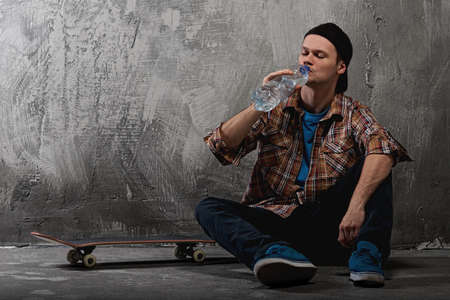 Young man with a skateboard drinking water photo