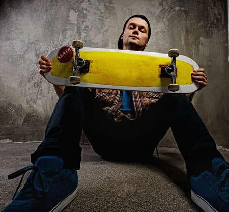 ni�o en patines: Hombre joven con una tabla de skate Foto de archivo