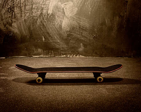Skateboard against grunge wall photo