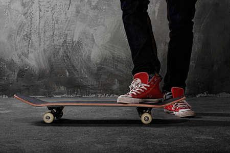 Benen in sneakers op een skateboard Stockfoto