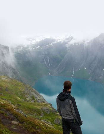 cliff edge: Man hiker in scandinavian landscape Stock Photo