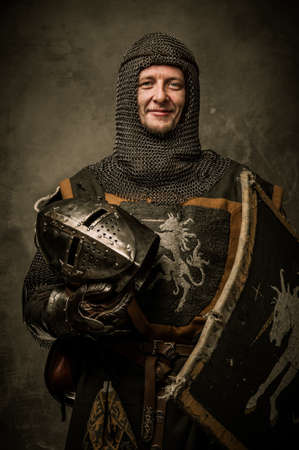 chain armour: Smiling medieval knight  holding helmet Stock Photo