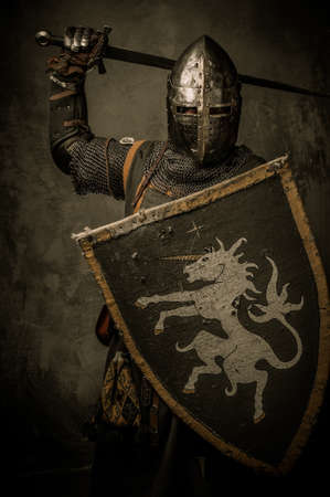 combative: Medieval knight on grey background Stock Photo