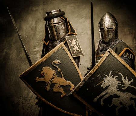 espadas medievales: Caballeros medievales sobre fondo gris Foto de archivo