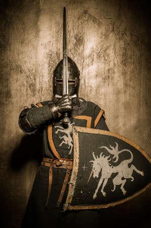 ナイト: 彼の顔の前で剣を保持している中世の騎士 写真素材