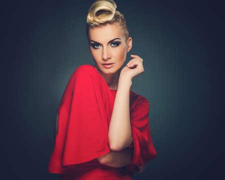 mujer pensativa: Mujer de moda en rojo con el peinado creativo