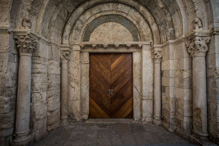 Wooden door in ancient archway photo