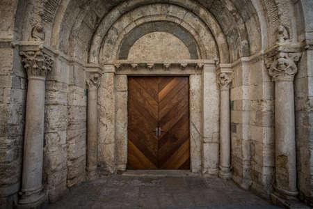고대의 아치 밑의 통로에있는 나무로되는 문