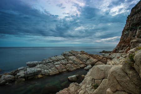 Gloomy sky over rocky shore Stock Photo - 16054656
