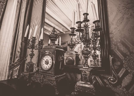 Antique clock and chandelier against mirror photo
