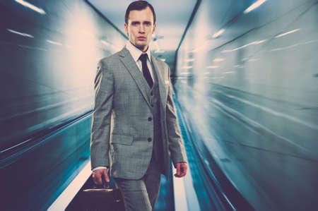Hombre en traje gris clásico con maletín de pie en la escalera mecánica