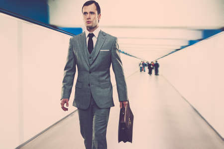 Man in classic grey suit with briefcase walking through corridor  photo