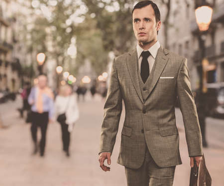 Man in classic grey suit with briefcase walking outdoors photo