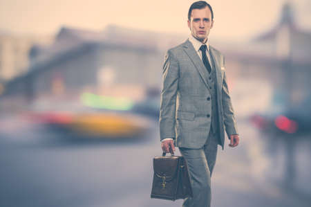 suit coat: Man in classic grey suit with briefcase  outdoors Stock Photo