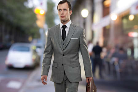 Man in classic grey suit with briefcase walking outdoors Stock Photo - 16086486