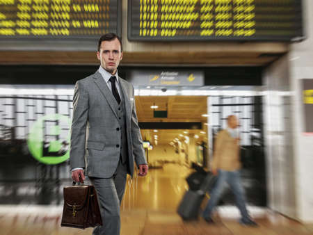 Man in classic grey suit with briefcase in airport photo