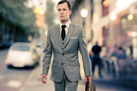 traje: Hombre en traje gris cl�sico con malet�n caminando al aire libre