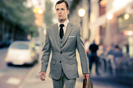 suit coat: Man in classic grey suit with briefcase walking outdoors