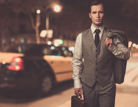 Man in classic grey suit with briefcase walking outdoors at night photo