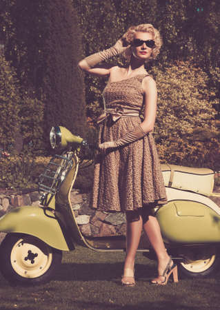 Woman in retro dress with a scooter Stock Photo - 16304869