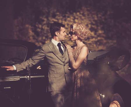 outdoor glamour: Couple near a retro car outdoors Stock Photo