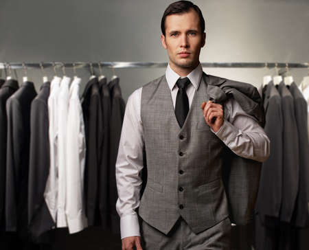 coat rack: Businessman in classic vest against row of suits in shop Stock Photo