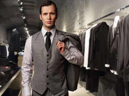 60s fashion: Businessman in classic vest against row of suits in shop Stock Photo