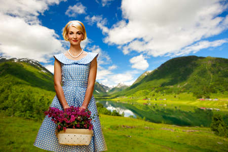 Lovely woman in  blue dress with flowers against lake view Stock Photo - 16305210