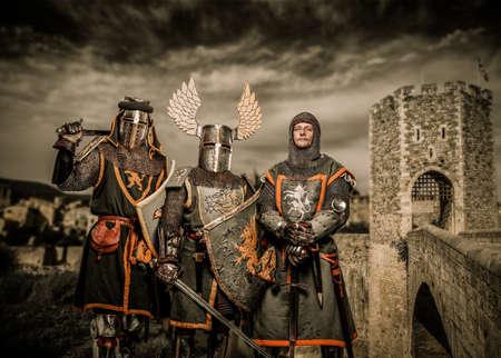 Three knight in armor against Romanesque bridge over river , Besalu