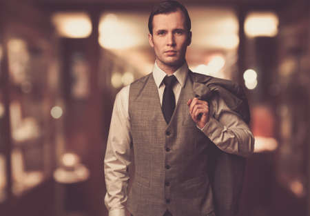 Man in waistcoat with jacket over his shoulder against blurred background Stock Photo - 16548610