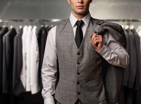 clothes rack: Businessman in classic vest against row of suits in shop Stock Photo