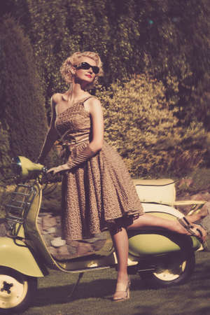 glamour woman elegant: Woman in retro dress with a scooter Stock Photo
