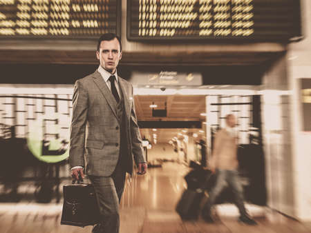 gray suit: Man in classic grey suit with briefcase in airport