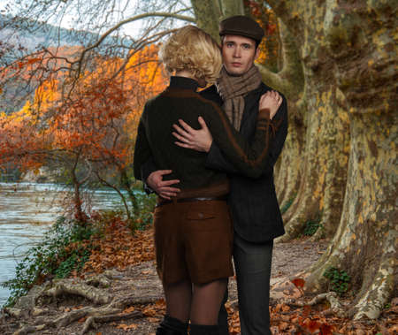 Elegant couple embracing near river in autumnal landscape photo
