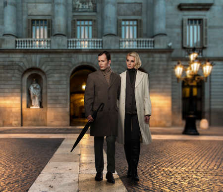 Elegant couple in coats against building facade in evening photo