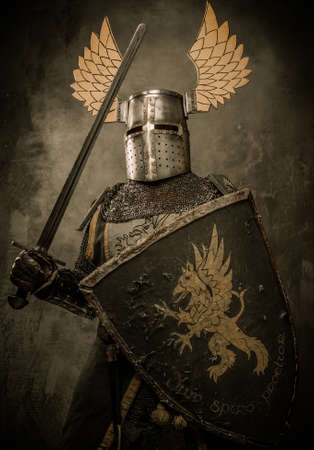 knights: Medieval knight with sword and shield against stone wall Stock Photo