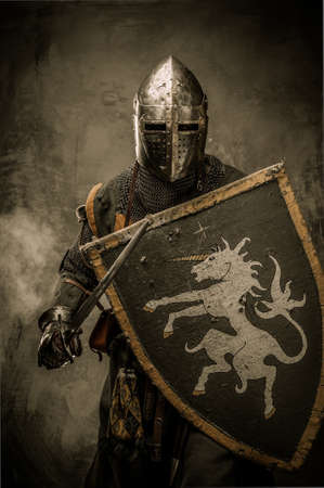 knight in armor: Medieval knight with sword and shield against stone wall Stock Photo