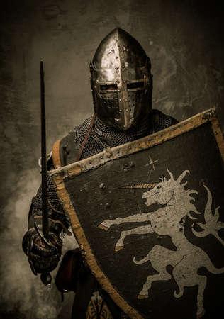 espadas medievales: Caballero medieval con la espada y el escudo contra la pared de piedra