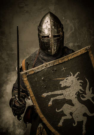 combative: Medieval knight with sword and shield against stone wall Stock Photo