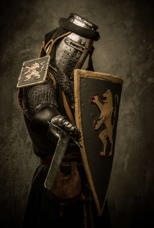 armored: Medieval knight with sword and shield against stone wall Stock Photo