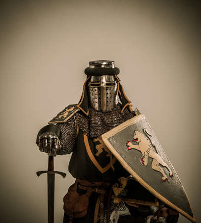 Kneeled medieval knight with sword and shield photo