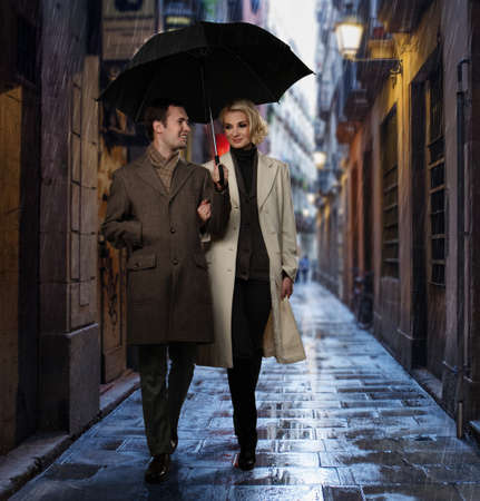 overcoat: Elegant couple with umbrella walking outdoors in the rain